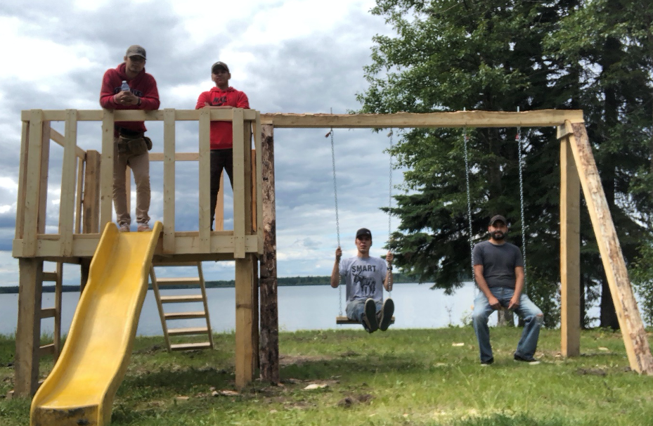 Youth trainees on left after completing the construction of a small playground