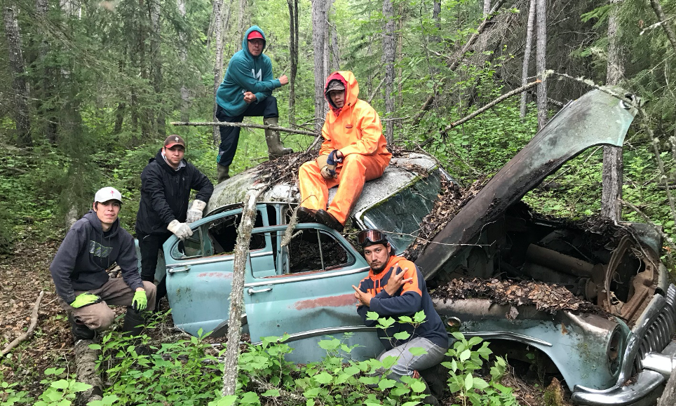 Youth trainees after finding a 1950 Buick Riviera while marking waypoints on historical trails